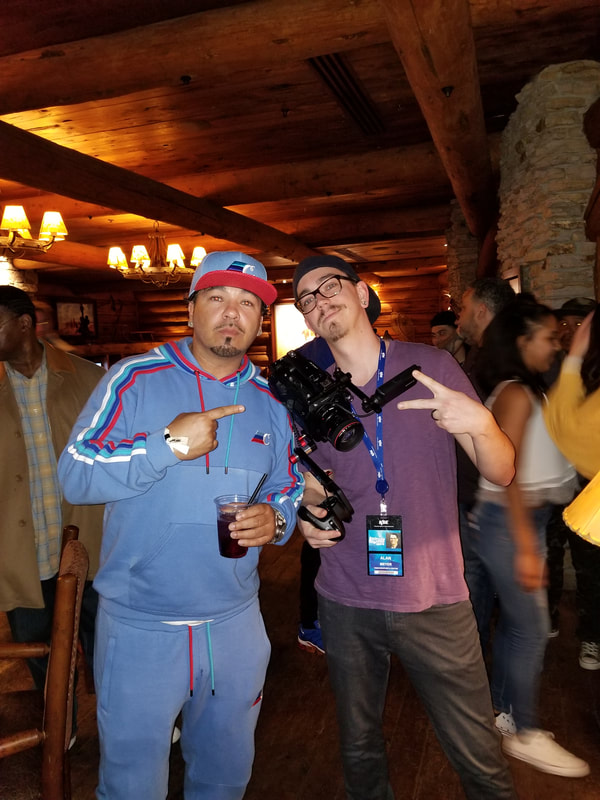 Alan Meyer posing with musician Baby Bash after performance at Denver Nuggets game.